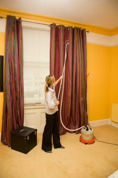 Drapery kit in use on curtains with steamer and carry case in shot