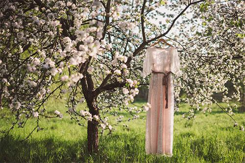 Lace wedding dress hung in blooming tree in spring garden
