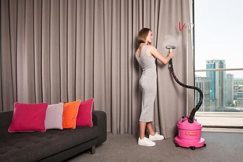 Lady uses Pink PRO580P steamer to steam curtains by a window
