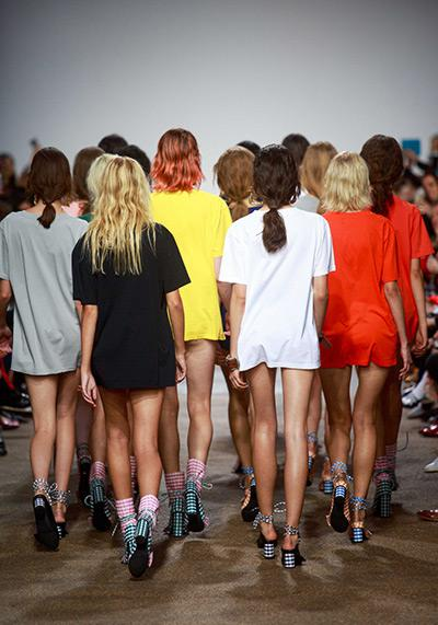 Rear view of group of models walking down catwalk