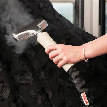 Nozzle in use steaming black embroidered dress